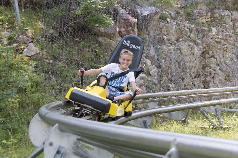 Auf der Rodelbahn in Buttes La Robella geht es mit Schwung den Berg hinunter